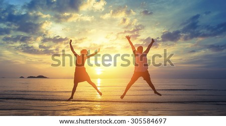 Silhouettes of happy young couple jumping on the ocean beach in the rays fantastic sunset. - stock photo