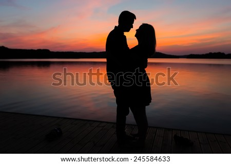 Silhouettes of hugging couple against the sunset sky. Vintage photo. - stock photo