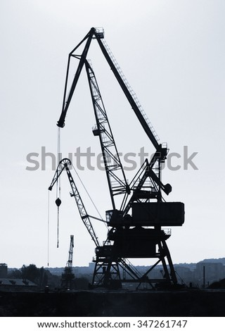 Silhouettes of industrial port cranes. Danube River coast in Bulgaria. Black and white vertical photo - stock photo