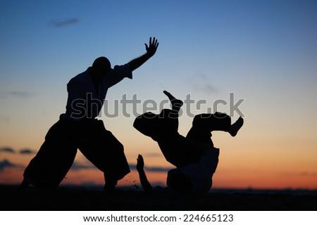 Silhouettes of Japanese warriors on sunset background - stock photo