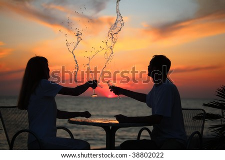 silhouettes of man and woman splash out drink from glass on sea sunset - stock photo