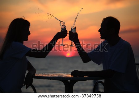 silhouettes of man and woman splash out drink from glass on sea sunset. focus on man - stock photo