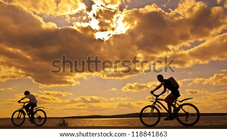 silhouettes of mother and child on bicycle against sunset sky - stock photo