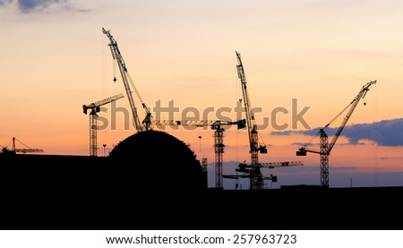 silhouettes of nuclear power plant under construction - stock photo