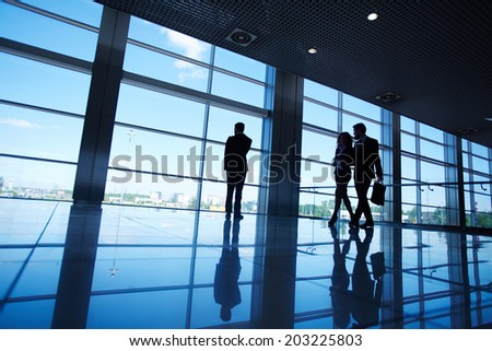 Silhouettes of office worker standing by the window and two business partners communicating while walking near by - stock photo