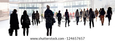 Silhouettes of people against the light background. Urban scene. - stock photo