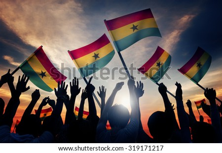 Silhouettes of People Holding Flag of Ghana - stock photo