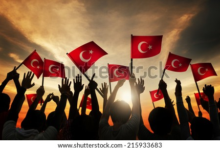 Silhouettes of People Holding the Flag of Turkey - stock photo