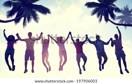 Silhouettes of People Jumping by the Beach - stock photo