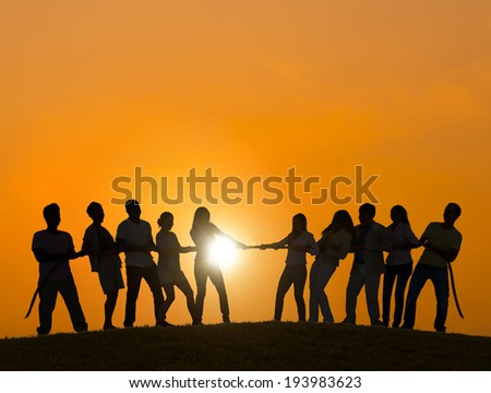 Silhouettes of People Playing Tug O Wars - stock photo