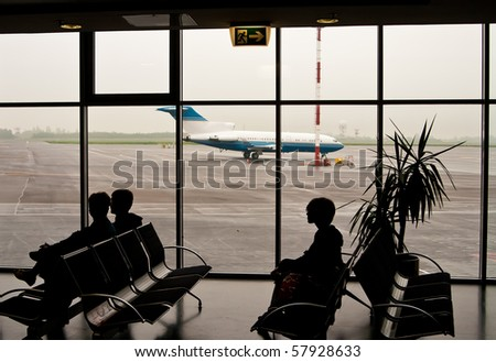 silhouettes of people sitting on chairs in the airport, in the window we can see the airplane - stock photo