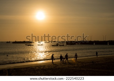 silhouettes of people walking on the beach at sunset, with fishing boats near a jetty. - stock photo