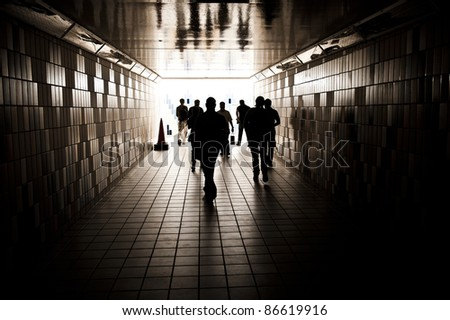 Silhouettes of random unrecognizable people walking in a tunnel. - stock photo