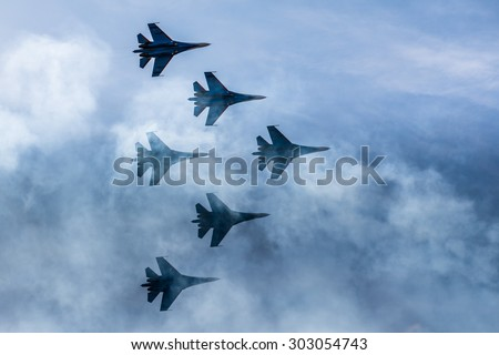 Silhouettes of russian fighter aircrafts SU-27 in the sky - stock photo