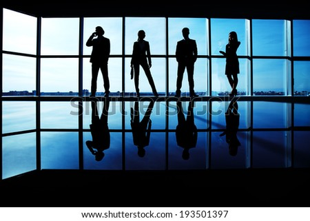 Silhouettes of several office workers standing by the window in line - stock photo