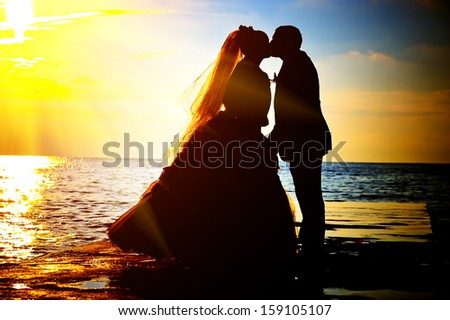 silhouettes of the bride and groom kissing on the background of sunset at sea - stock photo