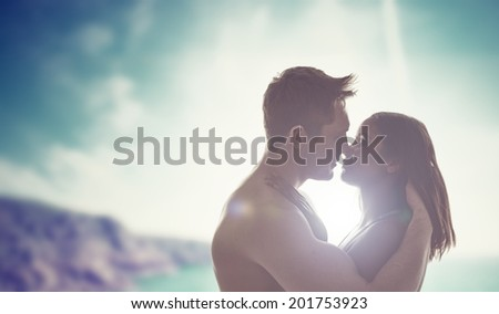 Silhouettes of the head and shoulders of a romantic young couple kissing backlit by the sun with a coastal backdrop - stock photo