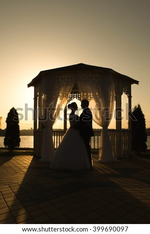 Silhouettes of the newlyweds at sunset, the outline of the figures. Lovers kiss. Faces of people do not see. Against the backdrop of a beautiful sunset. The bride dress is. - stock photo