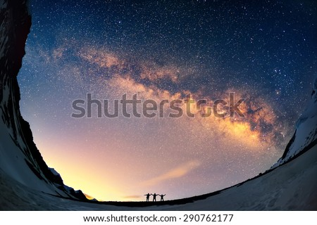 Silhouettes of the people standing together holding hands against the Milky Way in the mountains.  - stock photo