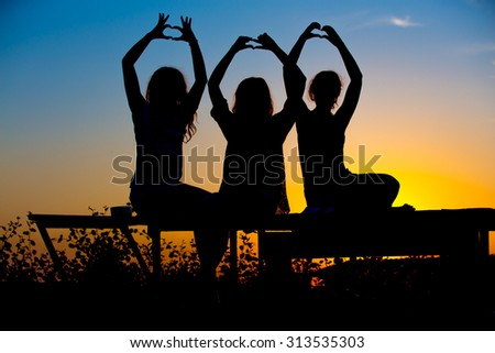 silhouettes of three young woman sitting on a sunset background and showing fingers heart symbol - stock photo