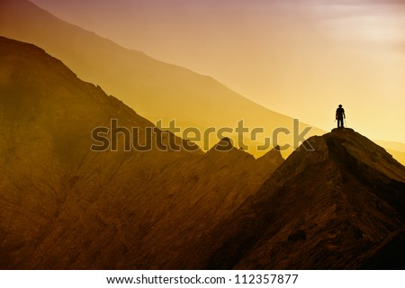 Silhouettes of tourists hiking on Bromo mountain - stock photo