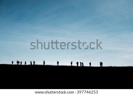 Silhouettes of travelers on the hill with blue sky - stock photo