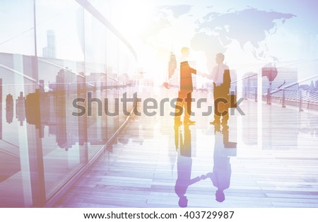 Silhouettes of Two Businessman Shaking Hands - stock photo