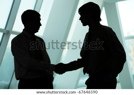Silhouettes of two businessmen handshaking and greeting each other - stock photo