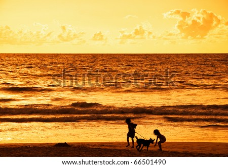 Silhouettes of two children playing on the beach against the sunset at sea - stock photo