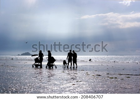 Silhouettes of two couples with prams walking on the beach and talking with each other during afternoon - stock photo