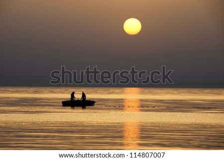 silhouettes of two fishermen fishing in boat on sea at gorgeous sunrise in Tunisia - stock photo