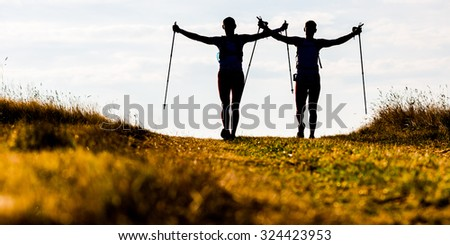 Silhouettes of two men during morning trail tun - stock photo