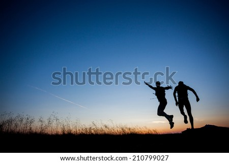 Silhouettes of two runners jumping during the sunrise - stock photo