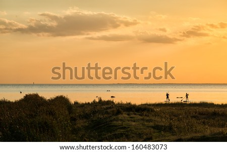 Silhouettes of two unidentified windsurfers landing at beach meadows in Bunkeflostrand south of Malmo, Sweden. These historic beach meadows are several thousand year old pastures. - stock photo