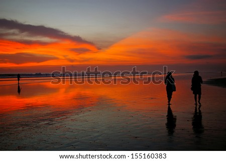 Silhouettes of two young women walking on the beach at sunset, Bali, Indonesia. - stock photo