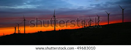 Silhouettes of wind turbines at sunset - the colors manipulated - stock photo