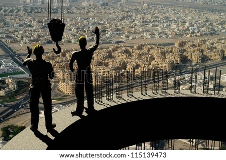 Silhouettes of workers against the background of the city. - stock photo
