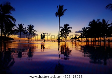 Silhouettes of young couple at scenic sunset on tropical beach - stock photo