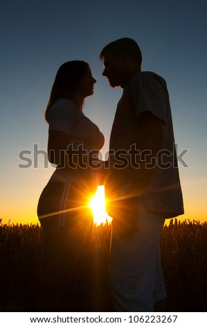 Silhouettes of young couple at sunset on beautiful summer day. - stock photo