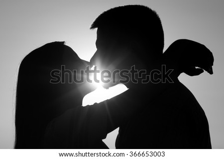 Silhouettes of young couple kissing on sunny summer day. - stock photo