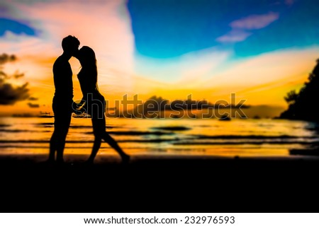 silhouettes of young loving couple on bright sunset sky and sea background - stock photo