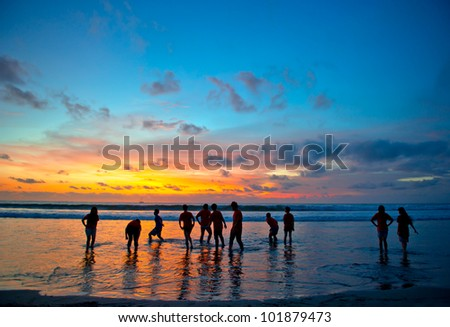 silhouettes of young people at famous sunset beach in Kuta, Bali, Indonesia - stock photo