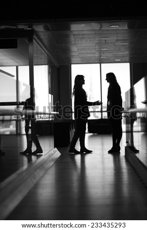 Silhouettes of young women talking in the office corridor - stock photo
