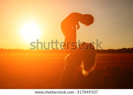 Silhouettes on sunny sky. Adorable blond kid boy and his mother having fun on yellow hay field in summer. Happy family of two enjoying nature and togetherness. Boy riding on mum. - stock photo
