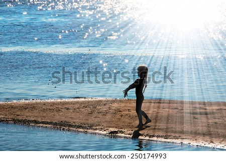 Silhouetto of a little girl in counter light on a river bank - stock photo