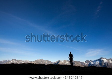 Silhoutte of a mountain hiker, big copy space - stock photo