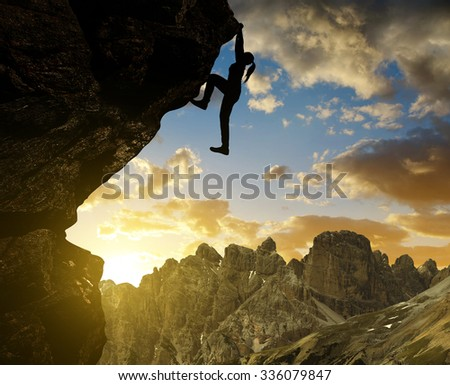 Silhoutte of girl climbing on rock at sunset in Sexten Dolomites, South Tyrol, Italy - stock photo