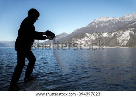 Silhoutte of man pouring ashes from an urn into a lake - stock photo