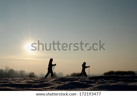 Silhoutte of people doing wintersport - stock photo