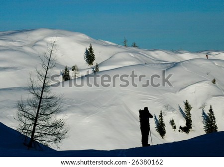 Silhuete on a woman with backback in winter mountains - stock photo
